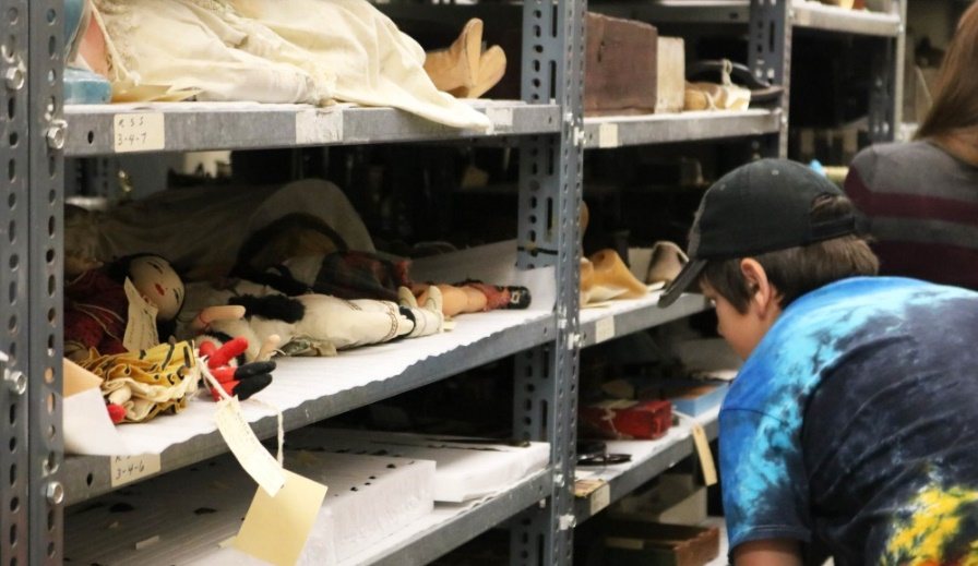 Young person in baseball cap looks at artifacts on a shelf in museum storage.