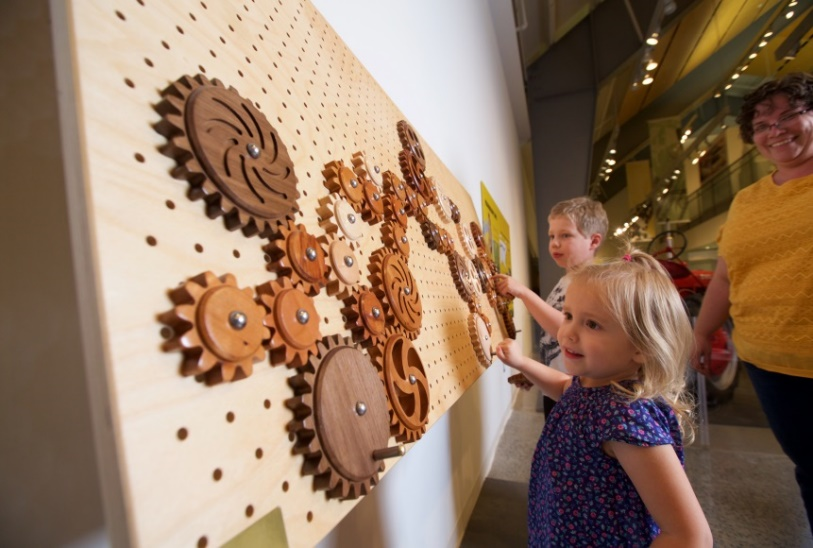 Two children turn gears on an interactive gear wall.