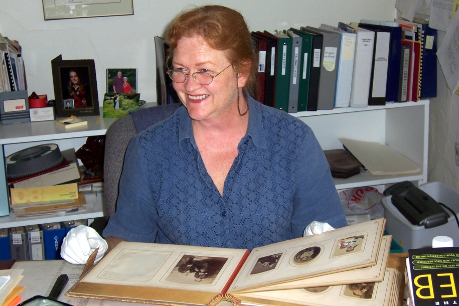 Rona Rustige seated at a desk examining a photo album and wearing white gloves.
