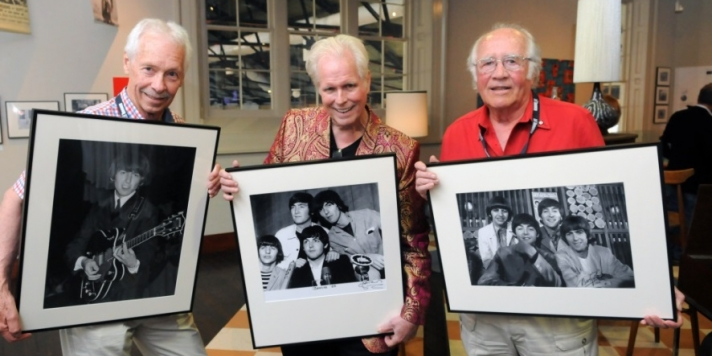 Three men holding balck and white photographs of the Beatles