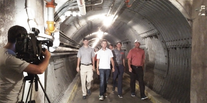 A group of men being filmed as they walk through the Diefenbunker tunnel
