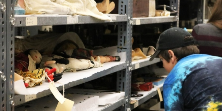 A young person in a baseball cap looks at artifacts on a shelf in museum storage.