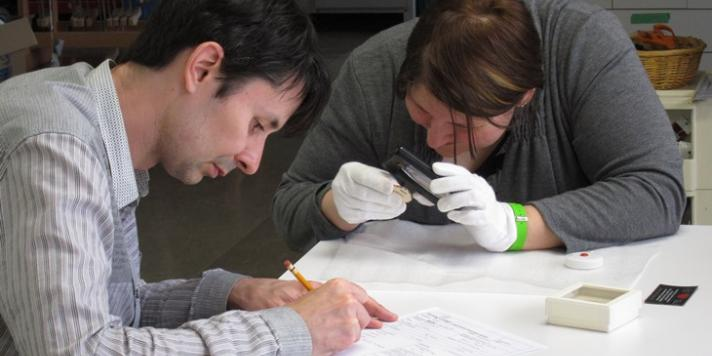 Two participants at the Artifacts course examine and condition report a small object