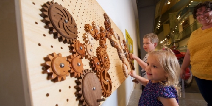 Two children play with a wooden gear interactive.