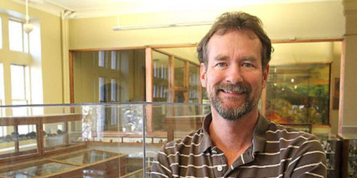 Mark Badham posing next to a large gold specimen in the Miller Museum of Geology
