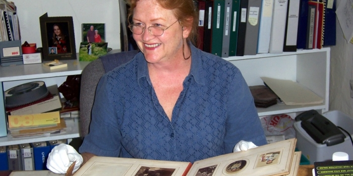 Rona Rustige seated at a desk examining a photo album while wearing white gloves.