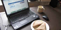A laptop open on a desk with a sandwich and a mug next to it.